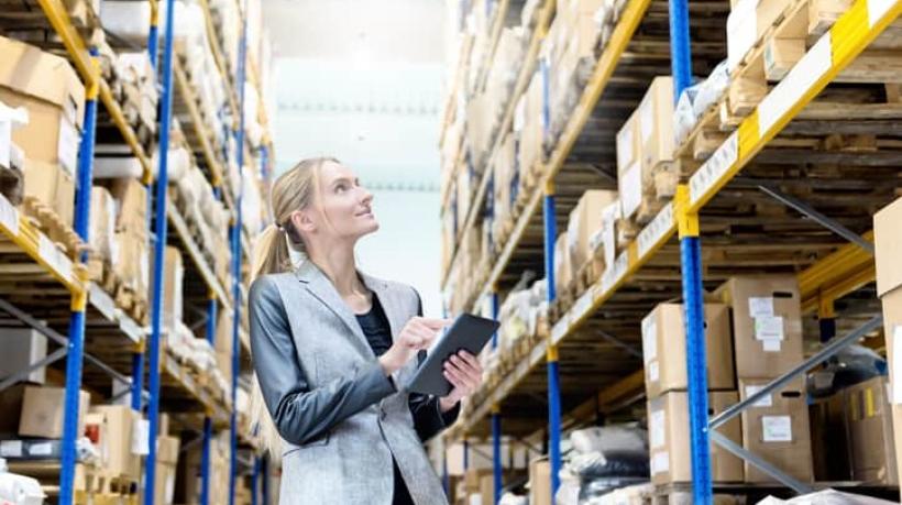 Mulher com ipad em depósito de caixas logístico