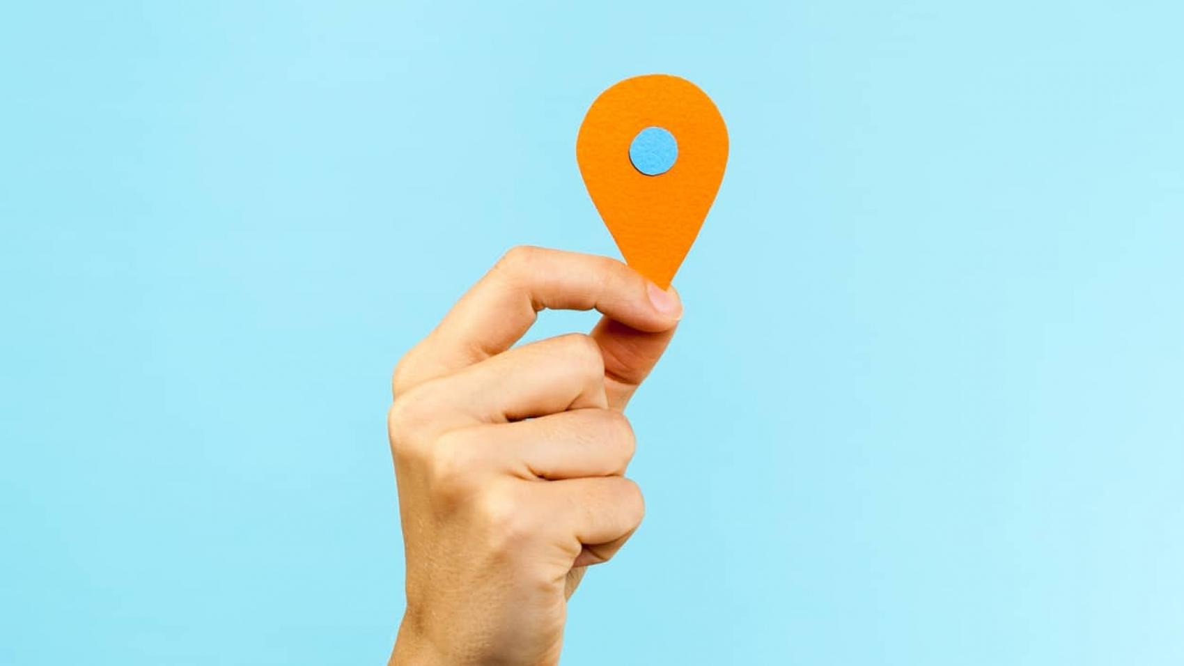 Mão segurando sinal de localização