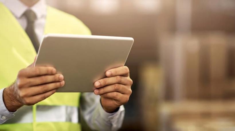Mão segurando tablet em galpão logístico
