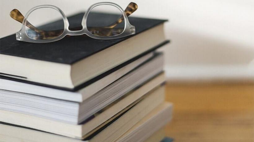Óculos em cima de pilha de livros